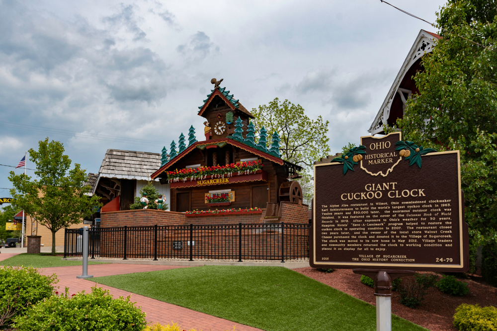 Ohio historical marker in Amish Country Ohio explaining giant cuckoo clock with German-inspired building in background.