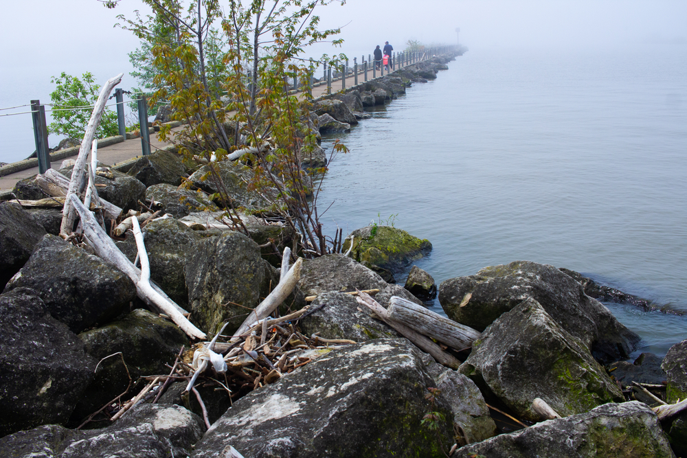 Boardwalk at Lakeview Park with rock outcroppings and calm waters of Lake Erie.
