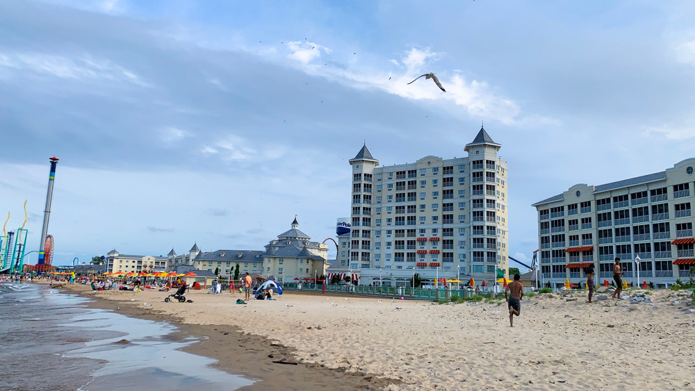 White sandy beach in Ohio with Cedar Point Hotels in background.
