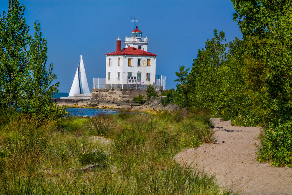 Sandy beach with green brush and red lighthouse with red roof in distance.