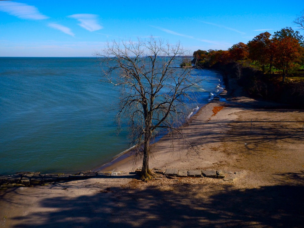 Ohio beach with sandy shoreline  with lake water lapping on shore.