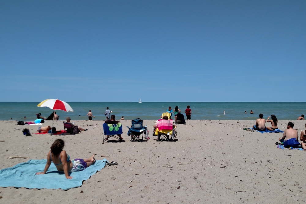 Sandy Ohio beach with people sitting in sun, Lake Erie waters and tiny sailboat on horizon.