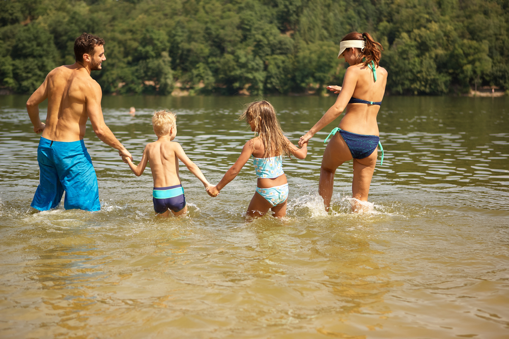 Family of 4 splashing and laughing in lake waters.