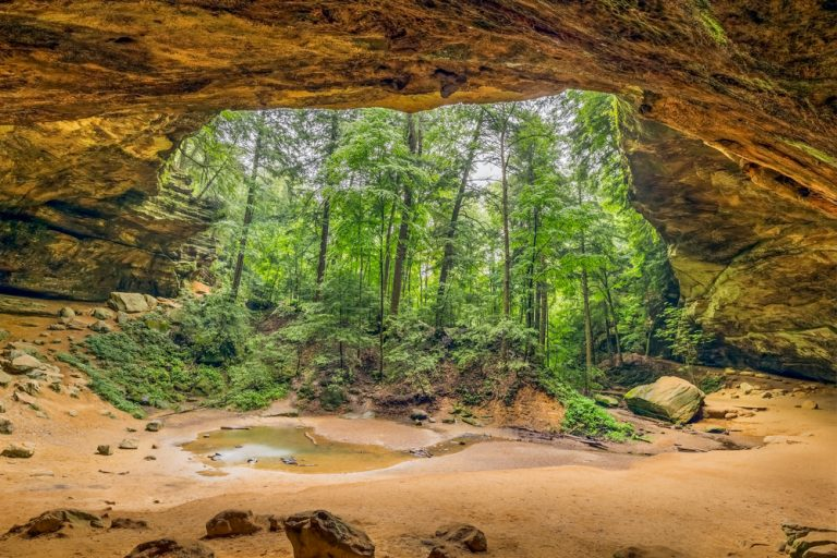 sandy cave opening with view of tall green trees best hikes in Ohio