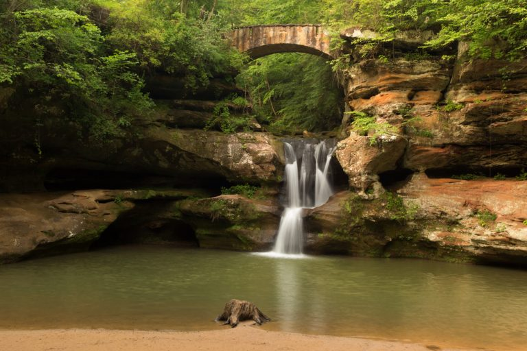 Best hikes in Ohio often lead to beautiful multilevel waterfalls into green pool of water.