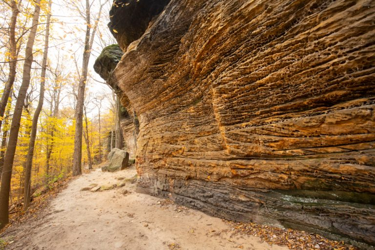 steep brown rocks with yellow trees in fall best hikes in Ohio at Ledges Trail in national park.