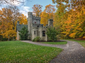 Photo of romantic European-inspired gothic castle in Ohio surrounded by autumnal trees with a large green front yard.
