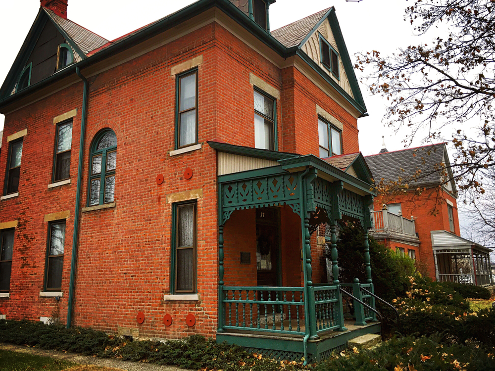 The Thurber House is one of the haunted Places in Ohio to visit. Photo of red brick house with green accents including ornate front porch.