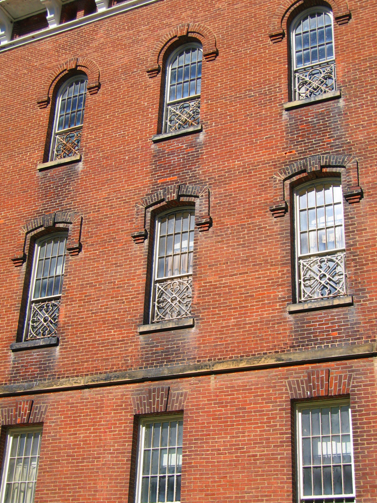 Close up photo of side old red brick building with ornate windows, an asylum Ohio haunted place that will creep you out.