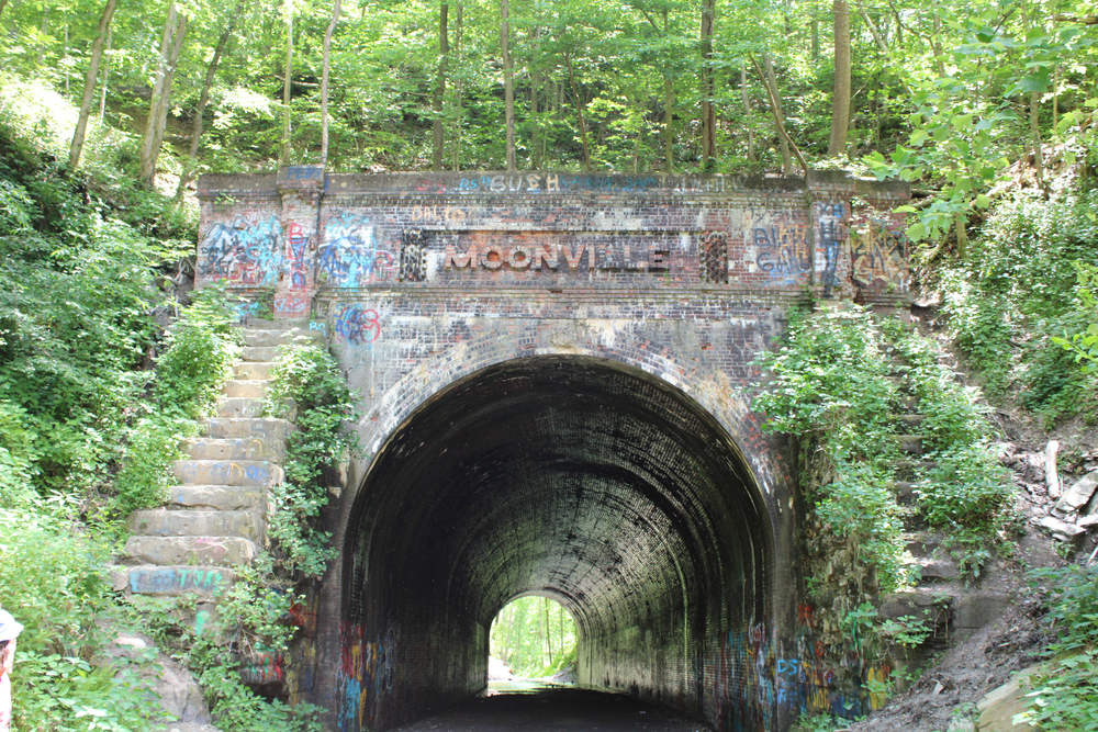 Creepy Moonville tunnel with overgrown trees and steps on either side of the stone archway. One of the haunted places in Ohio.
