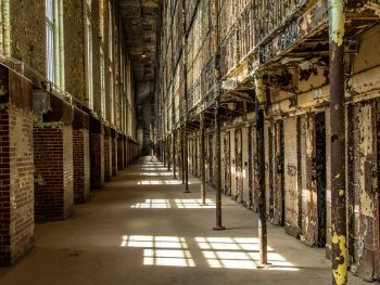 Dilapidated hallway of the Ohio State Reformatory with chipped paint and heavy doors of cells visible.