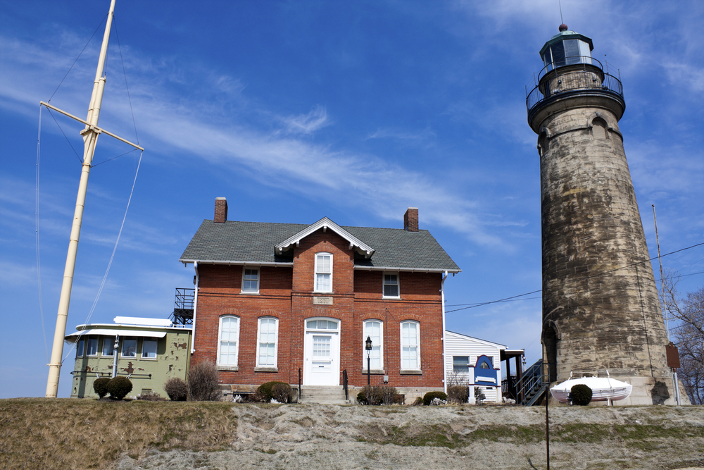 Photo of red brick building with stone lighthouse. A feline presence is felt at the Old Fairport Lighthouse one of the haunted places in Ohio.