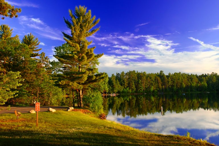 Green trees surrounding clear blue lake Northwoods, Wisconsin.