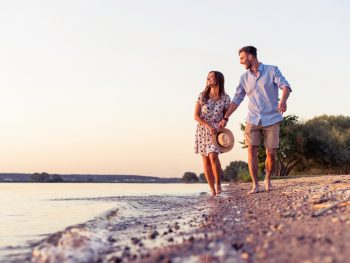 Smiling couple walking on rocky beach with water on left and trees in background.