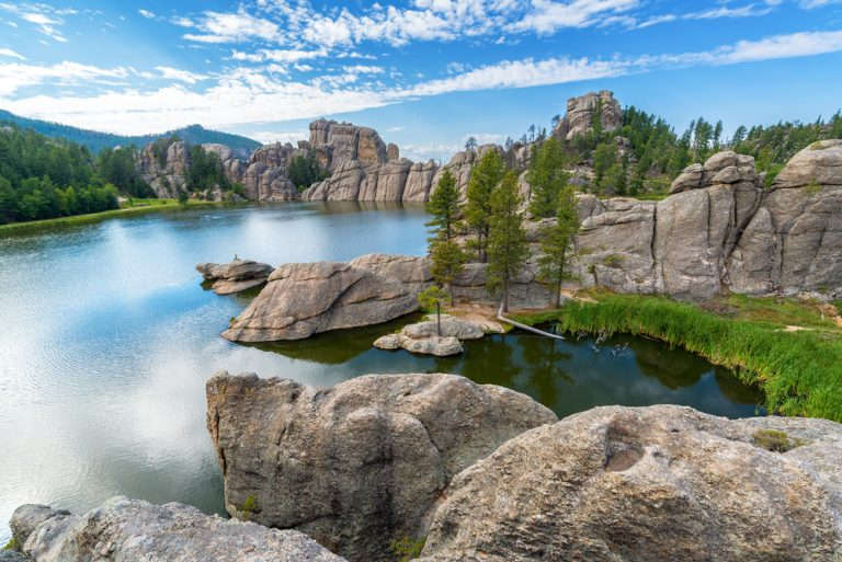 Clear blue lake surrounded by large rocky outcroppings.