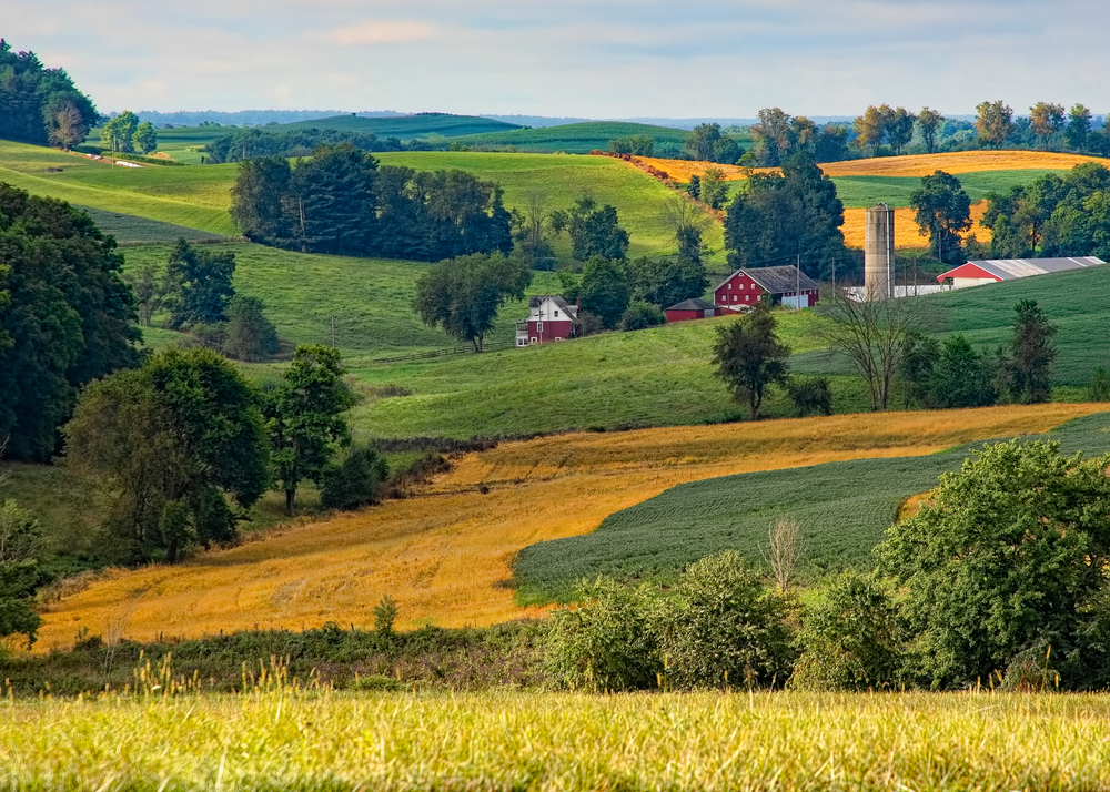 Photo of rural roaming hillsides with red barn with silo.