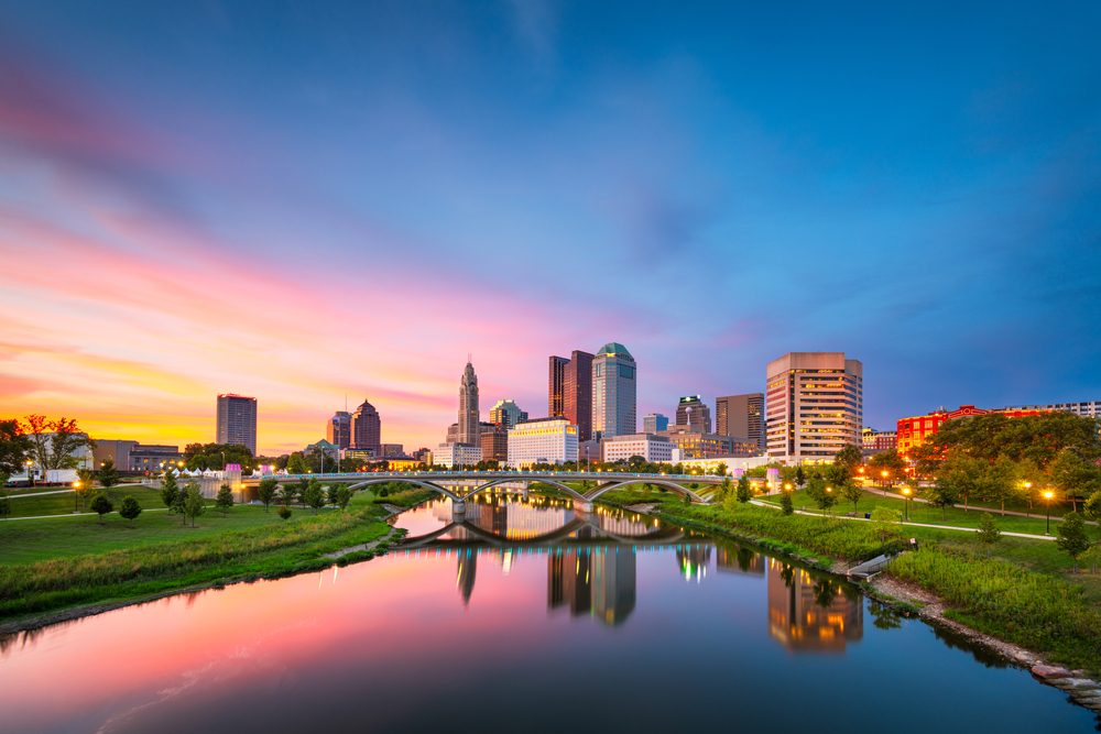 Twinkling cityscape of Columbus A romantic getaway in Ohio, at twilight with Ohio River in foreground.