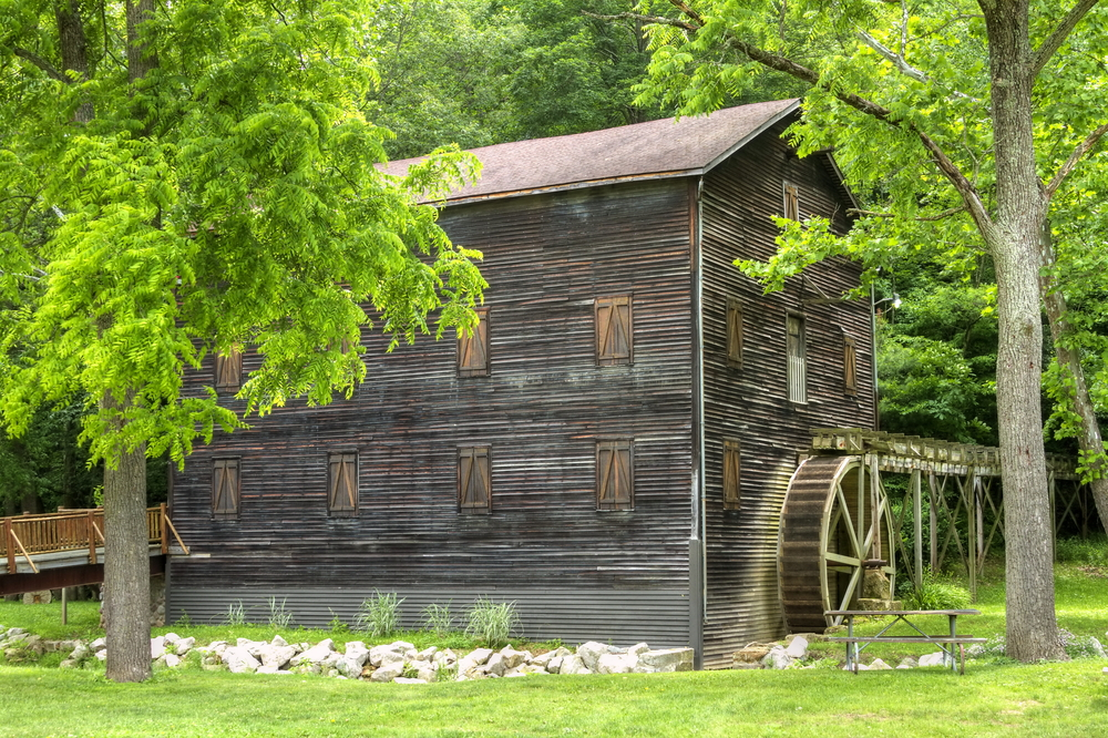 Large wooden structure with water wheel surrounded by lush greenery in Loudonville.