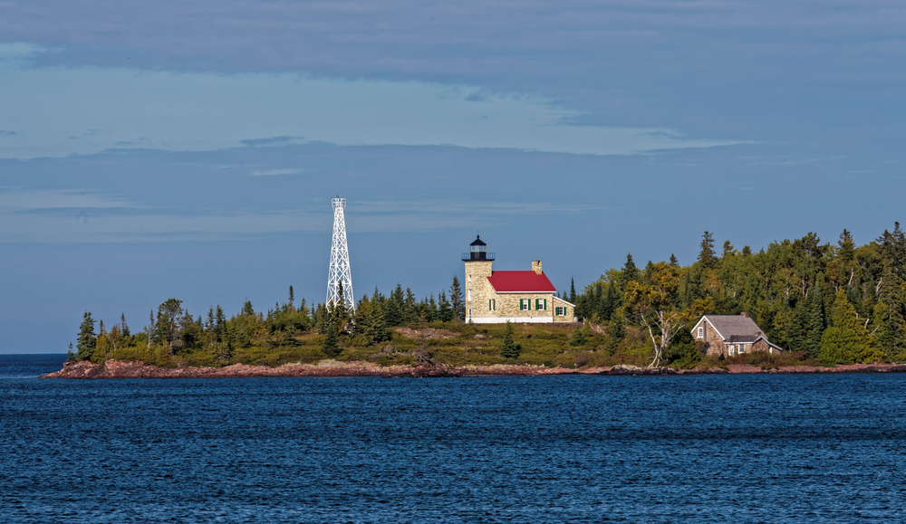 Copper Harbor lighthouse with red roof surrounded by deep blue waters.