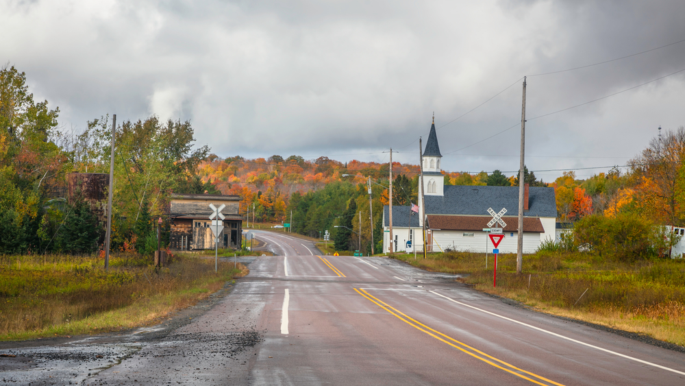 An old church with steeple and railroad crossing with brilliant autumn colors on trees in background in Covington MI