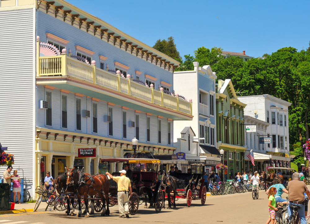Horse drawn carriage with vintage buildings in background of Mackinac Island.