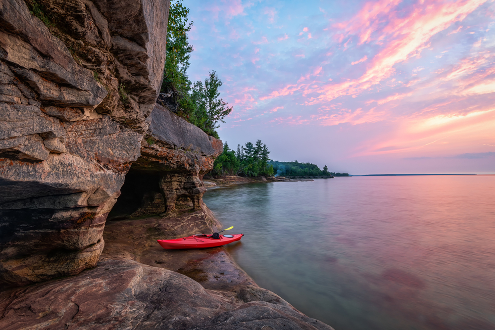 Red kayak on lake next to craggy rocks with gorgeous sunset in sky in Munising.