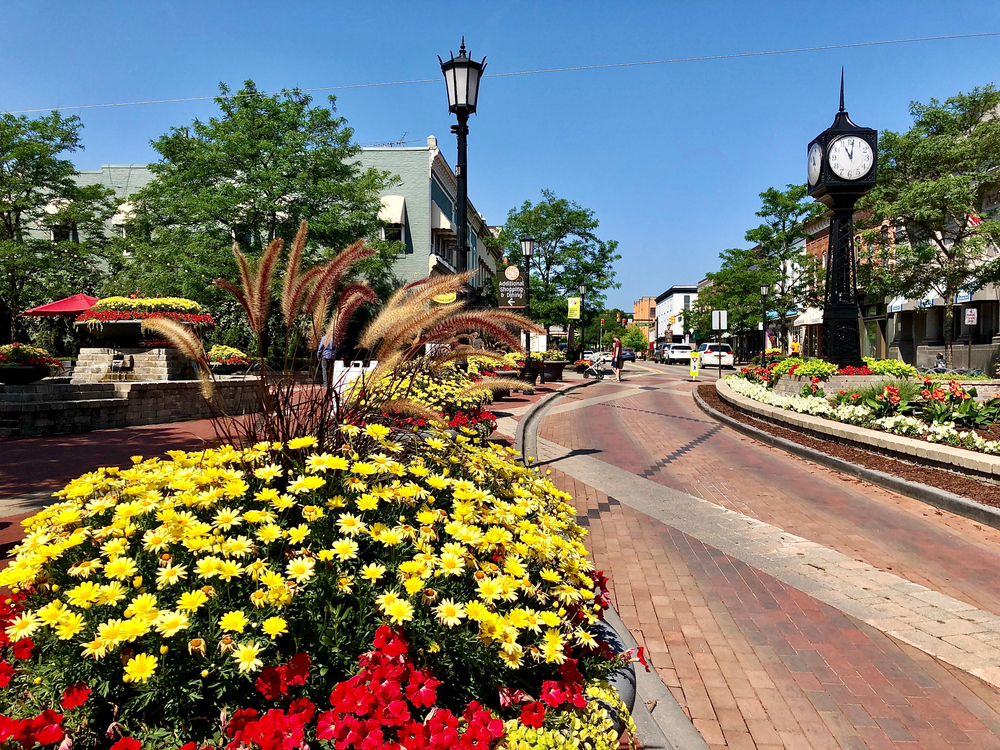 Beautiful red brick street in Northville with blooming flowers and vintage clock.