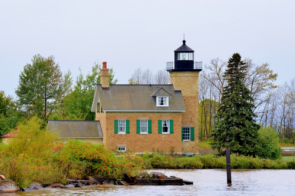 Iconic orange-brick lighthouse with green shutters of small town in Michigan Ontonagon