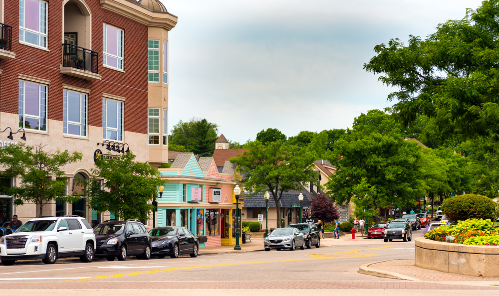Vintage main street in small town in Michigan, Plymouth with bright buildings and cars parked.