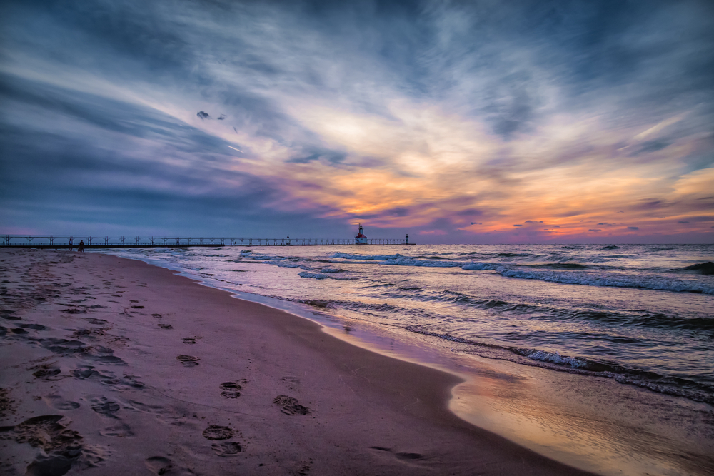 Stunning sunset seen from sandy beach of small towns in Michigan with lighthouse in background.