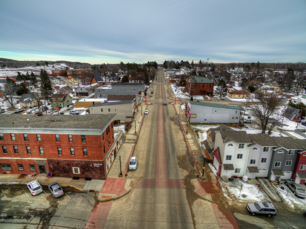 Small town Minnesota main street with red brick building in left foreground and colorful rowhouses in right foreground.