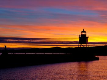 Sky lit at sunset with pink and yellow with lighthouse silhouetted in background with still water in foreground of Grand Marais MN
