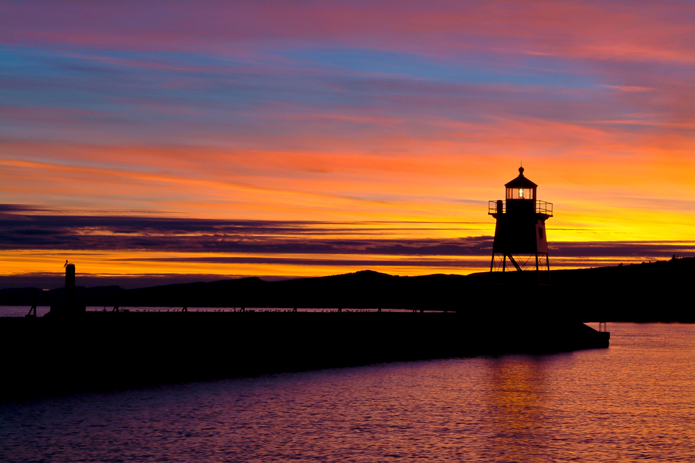 Lighthouse of small town in Minnesota with gorgeous orange/yellow sunset filling sky.