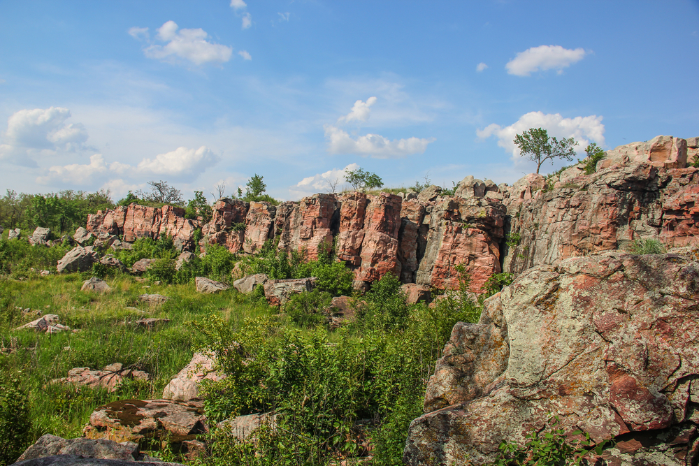 Pink Sioux Quartzite ridgeline in small town Minnesota with green brush in front of it and blue skies.
