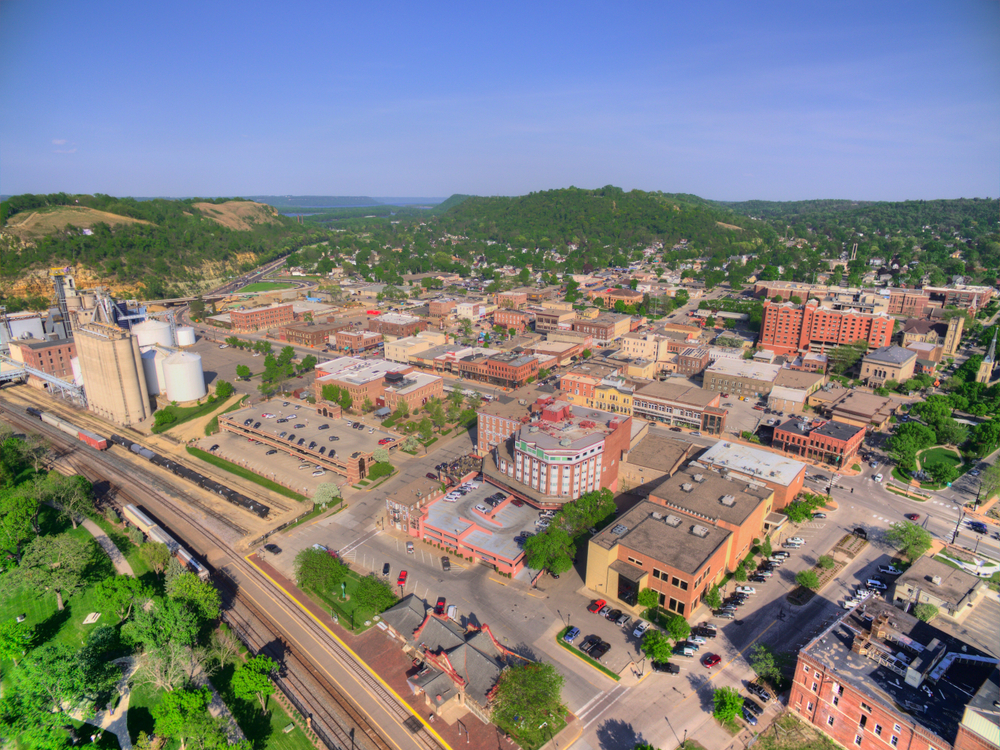 Aerial view of Minnesota small town with vintage buildings and rolling hills in background.