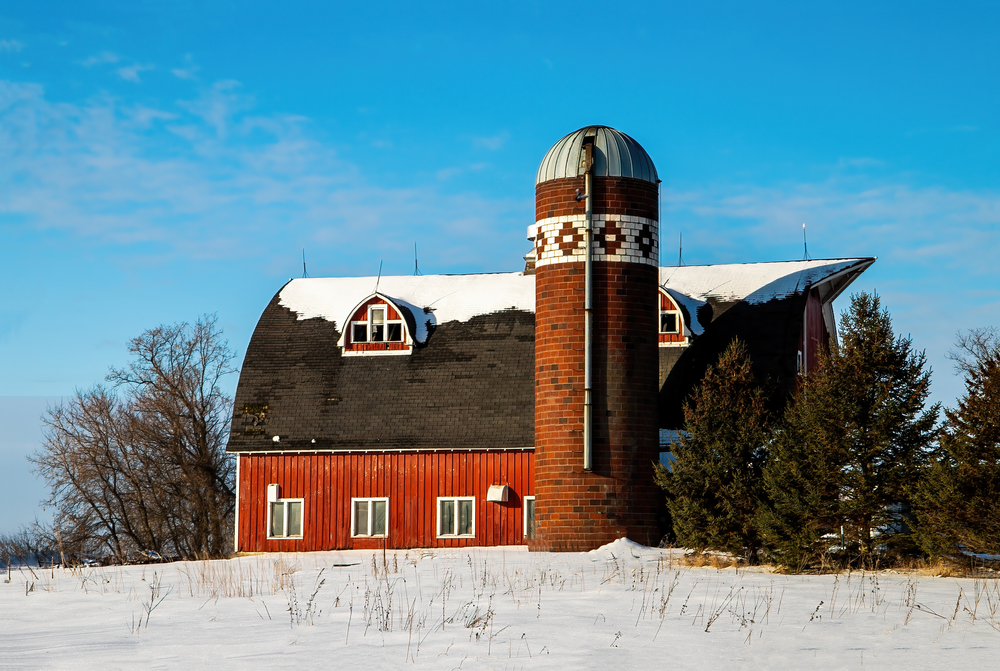 A red barn in Minnesota small town that has a quilt pattern in the bricks of the silo with snow in the foreground.