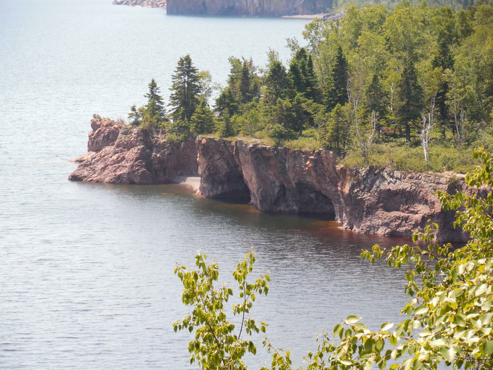 Spectacular scenery small town Minnesota with jagged cliffs topped with evergreen trees on shores of Lake Superior.