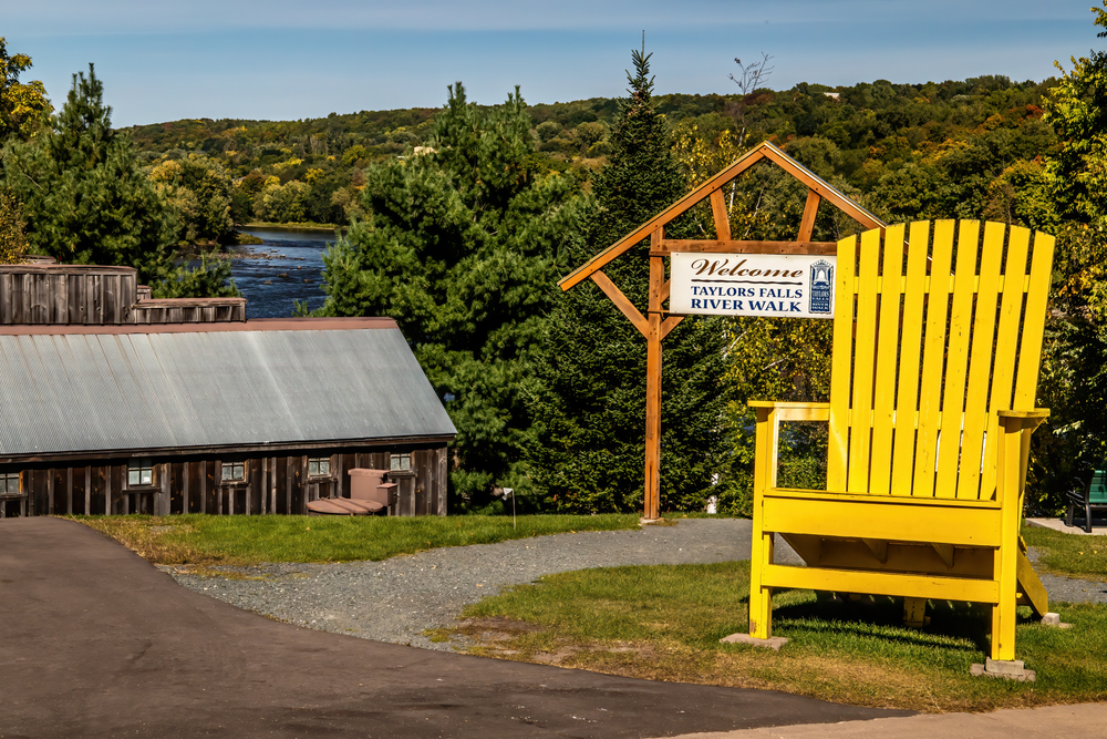 Large yellow Adirondack chair near welcome sign leading to Taylors Falls Riverwalk with water in background