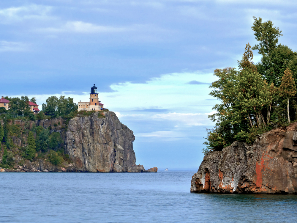 The Split Rock Lighthouse in Two Harbors Minnesota high up on stone cliff with blue waters below.
