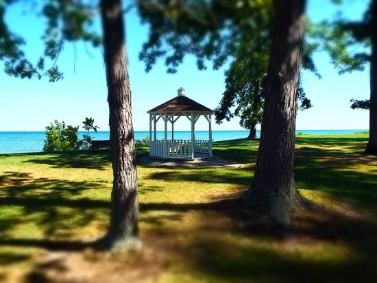 White gazebo located in park in Geneva-on-the-Lake, small town Ohio, with blue waters of Lake Erie in background.