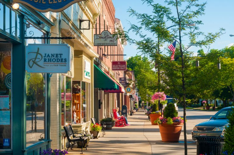 Pastel storefronts of downtown Hudson,  with flowering baskets everywhere. Small Town Ohio.