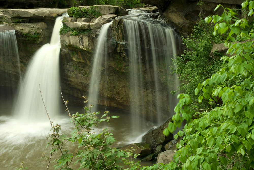 Cascading waterfall in Ohio rushed over large rock formations info water below. Green tree in foreground.