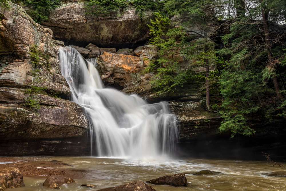 Waterfalls spilling down through rock ledges to water below.