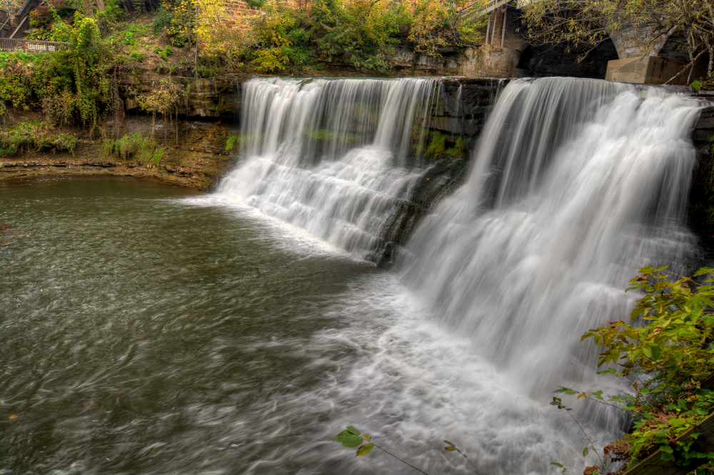 Chagrin waterfalls in Ohio - two cascading falls over rocks with trees and stone bridge in background.