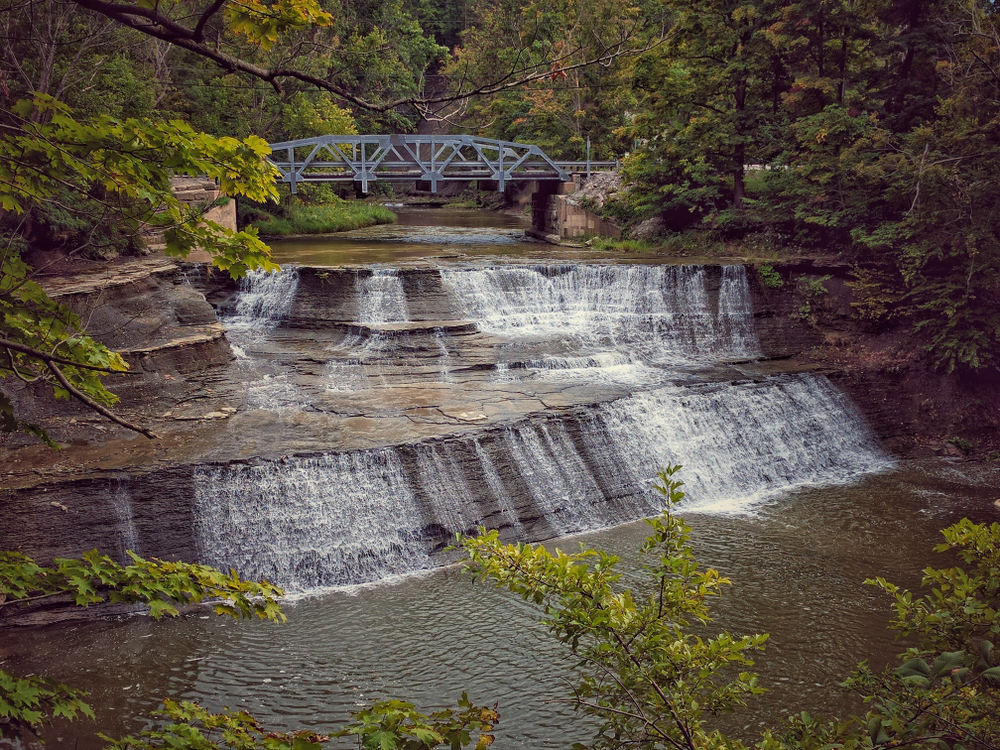 Paine waterfalls in Ohio are easy to get to - a series of cascading falls along two distinct sections with blue bridge in background.