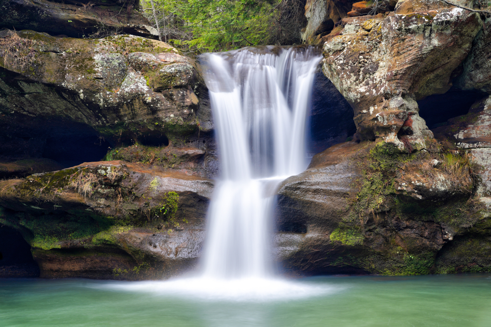 Water cascading down through rocks into pool of green water below