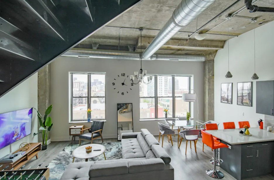 The interior of a loft penthouse in chicago that is painted white and has large windows that look out onto the city skyline