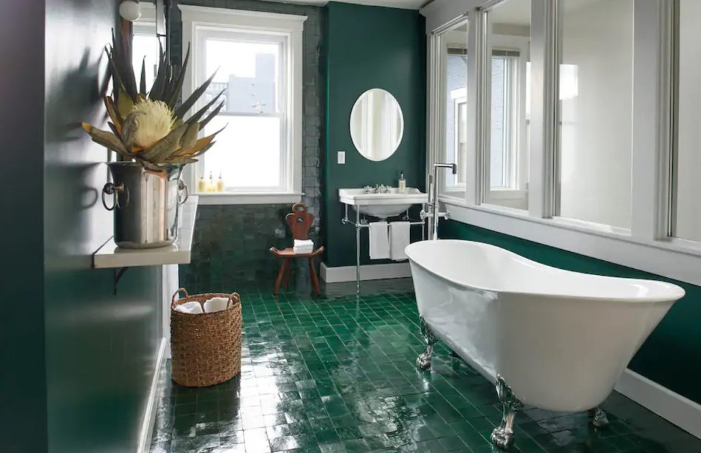 A luxurious bathroom with emerald green tiled floors, emerald green and stone walls, a claw foot bathtub, and windows one of the best airbnbs in the midwest