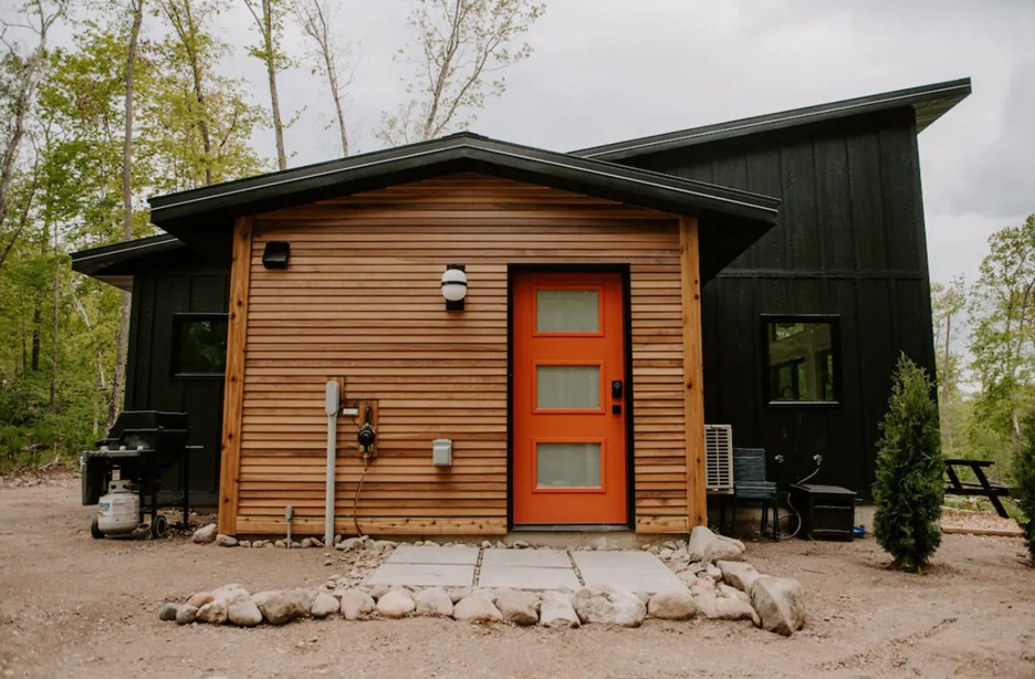 A large modern cabin with most of it painted black, but the area with the front door has natural wood and a bright orange door one of the best Airbnbs in the Midwest