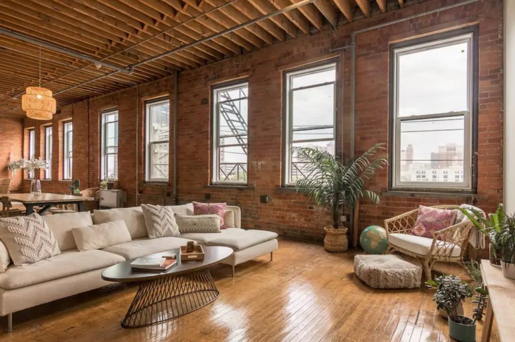 A large loft space with plenty of windows, exposed brick walls, exposed wood beam ceilings, and neutral decor in Detroit Michigan one of the best Airbnbs in the Midwest